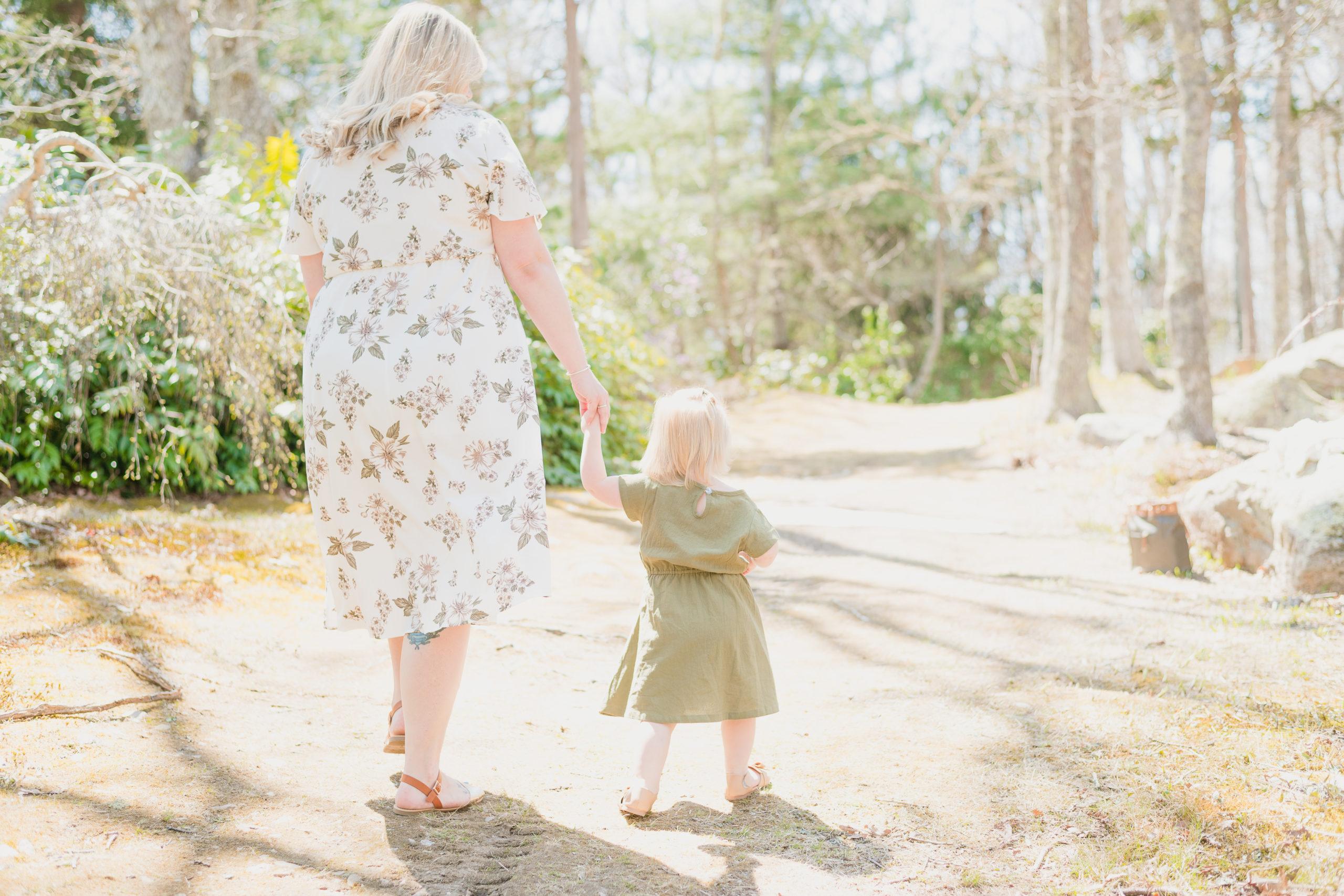 Mother and young daughter walking through Spohr Gardens wearing flowy dresses and holding hands during their mommy and me session. There is beautiful natural light coming through the trees.