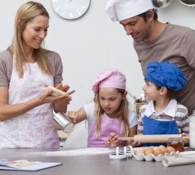 Mother and father helping children baking in the kitchen