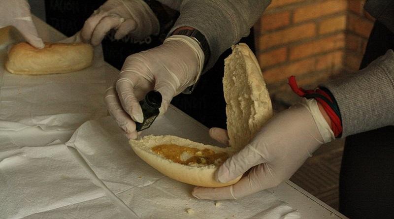 Primer plano de unas manos preparando el típico desayuno andaluz (pan con aceite) para celebrar el Día de Andalucía.