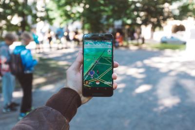Hand holding phone showing pokemon go