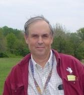 Hombre blanco con canas en camisa a cuadros en jersey granate con hierba verde y árboles en el fondo.