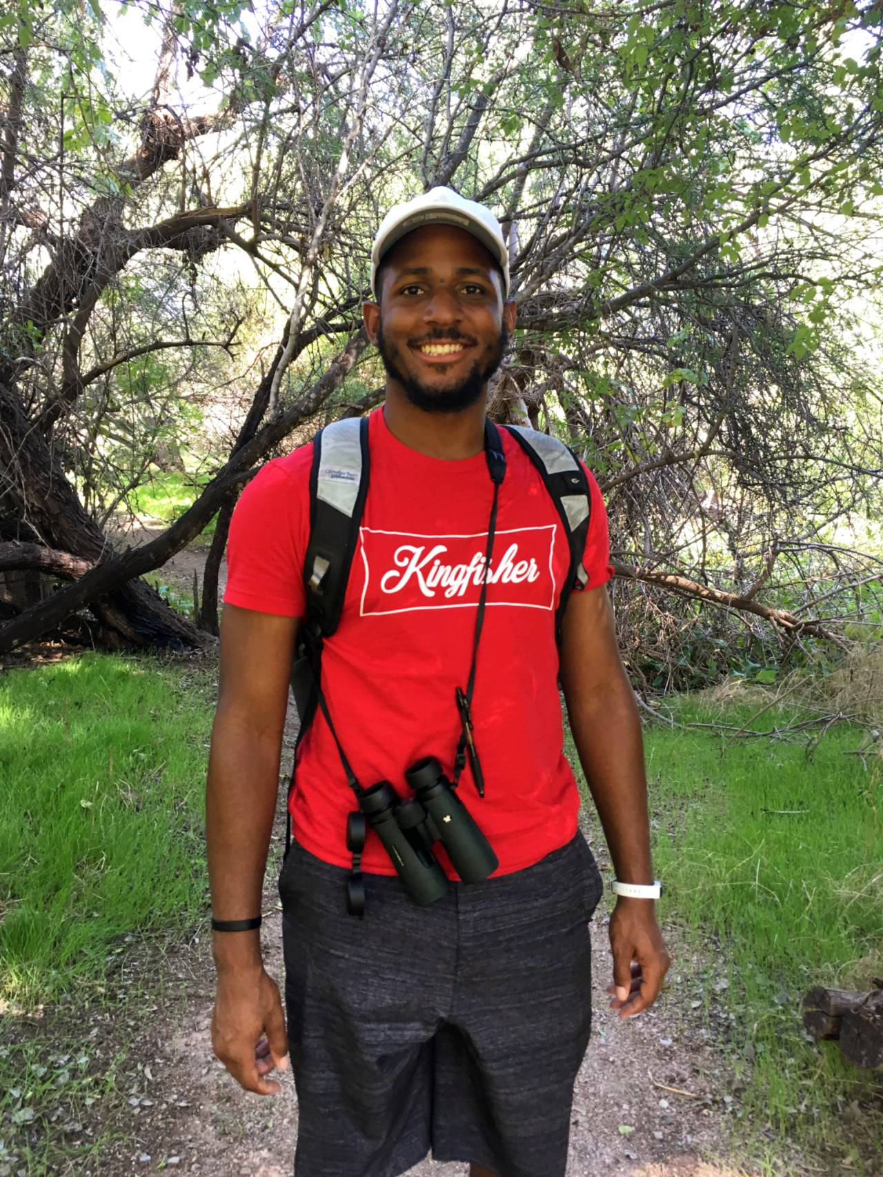 """Black man with beard in white hat, red shirt that reads, """"Kingfisher"""" in black shorts and binoculars."""