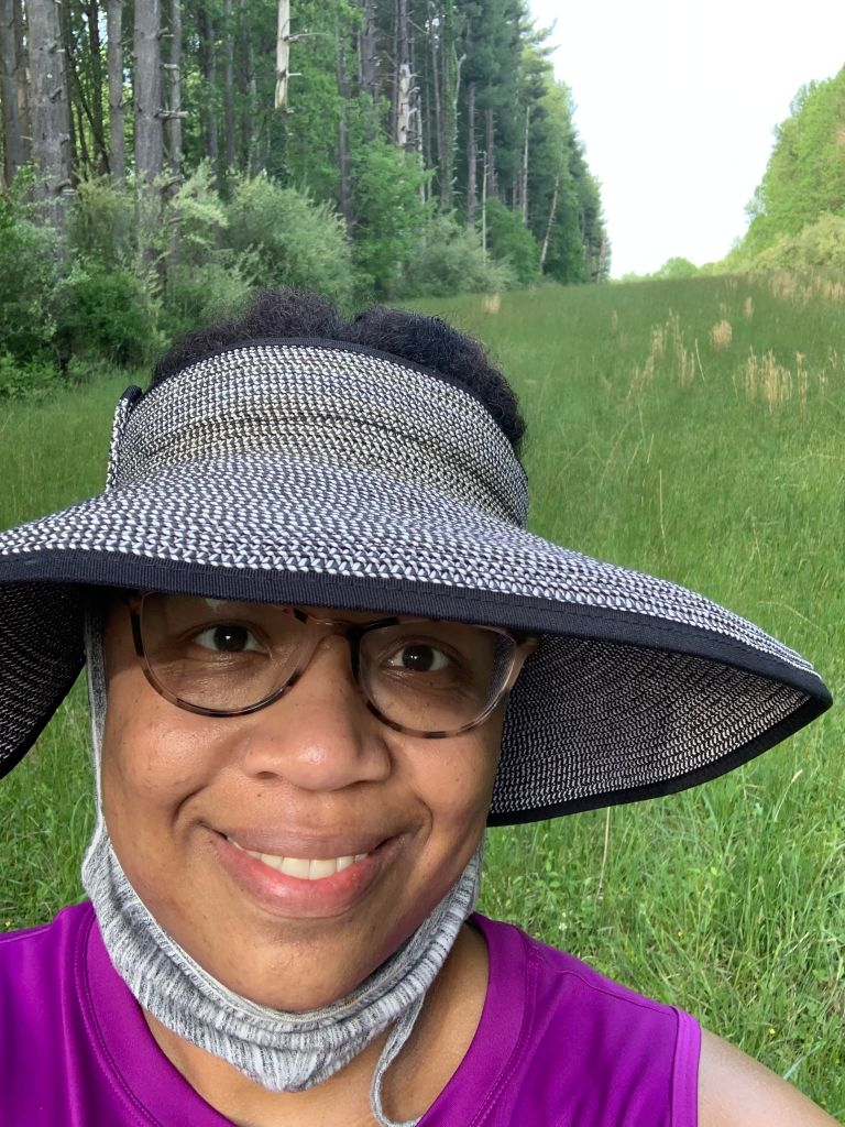 Black Woman in Glasses with hat on in green field lined with trees.