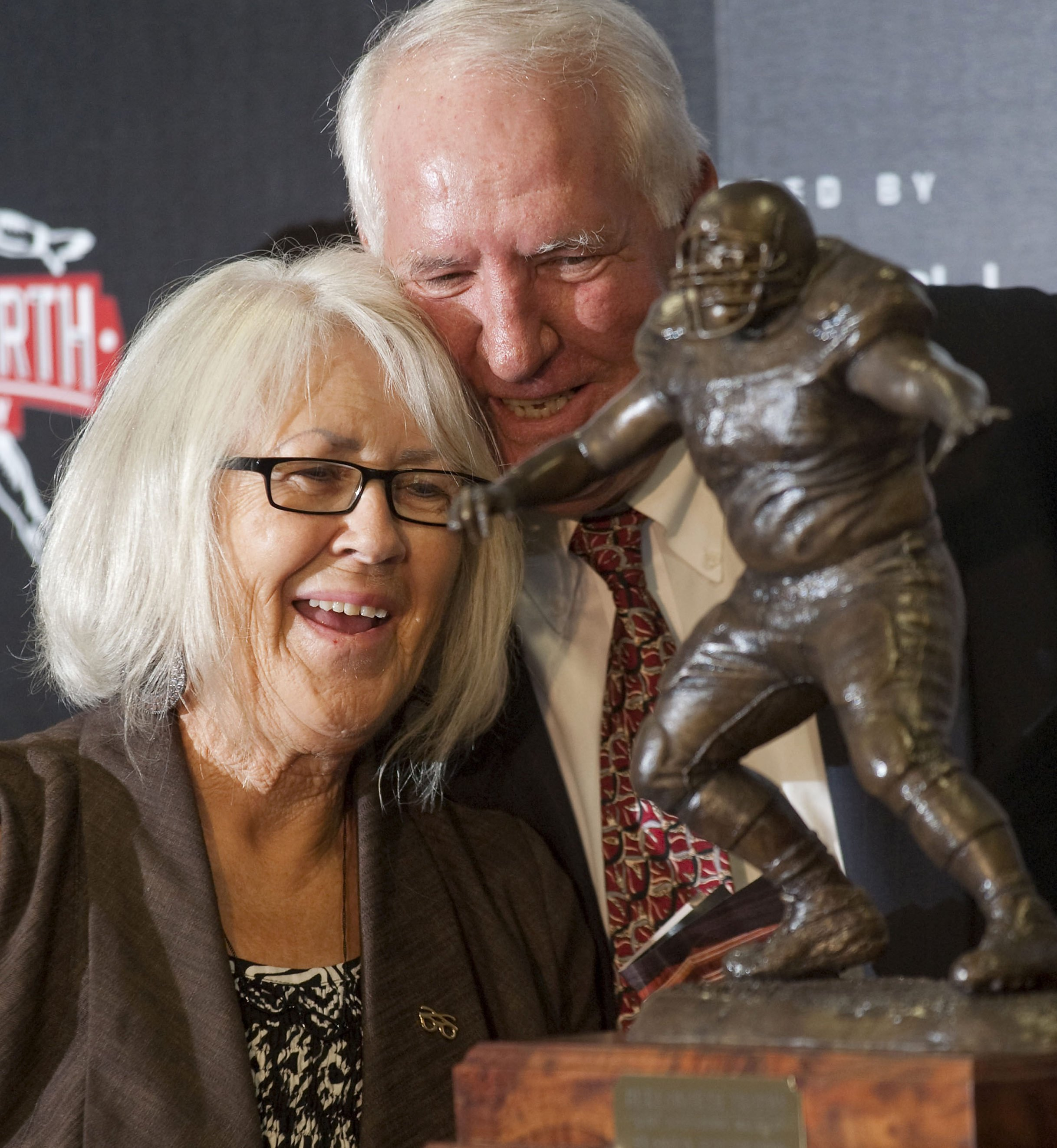Image result for Former Arkansas head Coach Danny Ford hugs Barbara Burlsworth in August 2010 in Fayetteville after the unveiling of the Burslworth Trophy in honor of her son, Brandon. The trophy is given annually to a college player who started his career as a walk-on. (AP photo by Beth Hall)