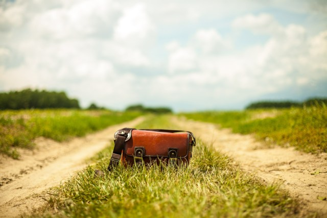 Red purse sitting on dirt road surrounded by grass