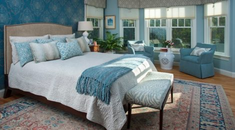 Soothing tones of blue, white, and a hint of coral create a haven for rest and relaxation in this master bedroom.