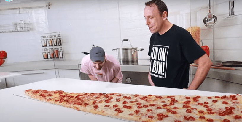 six-foot long slice of pizza and man going to eat it