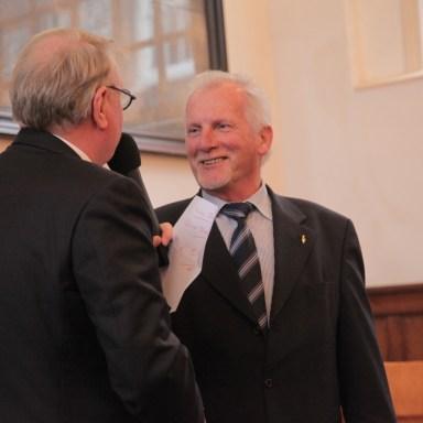 Voorzitter Piet van Meerveld (links) ontvangt van Jan Gils, voorzitter kerkenraad Prot. Gemeente Zunderdorp, een cadeau.