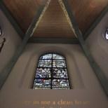 """Het mooie glas-in-lood-raam met daaronder de Bijbeltekst """"Schenk mij, God, een nieuw hart"""""""