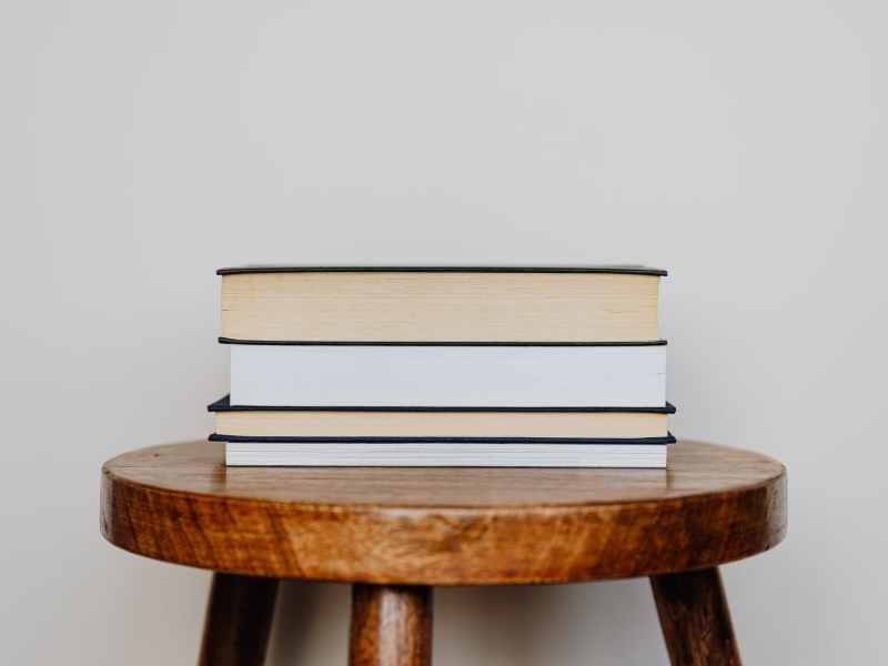 close up photo of stack of books on wooden stool