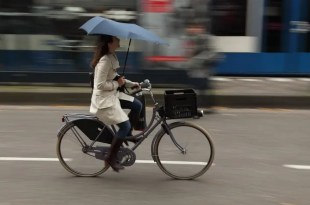 cycling in the rain with an umbrella in Amsterdam