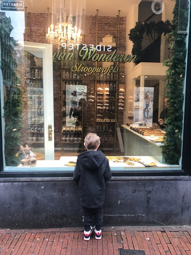 A little boy looking in the window at Van Wonderen Stroopwafels - a contender for the best stroopwafels in Amsterdam