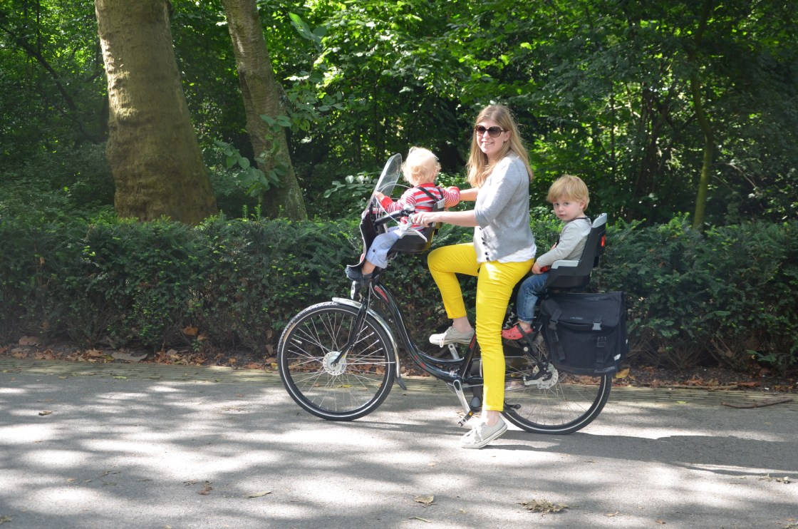A mum on a bike with a baby and toddler in the Vondelpark Amsterdam