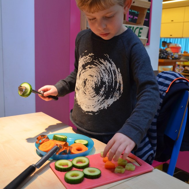 Toddler making his own food at the Kinderkookcafe Amsterdam