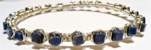 silver metal bangle with blue square beads wrapped in nests