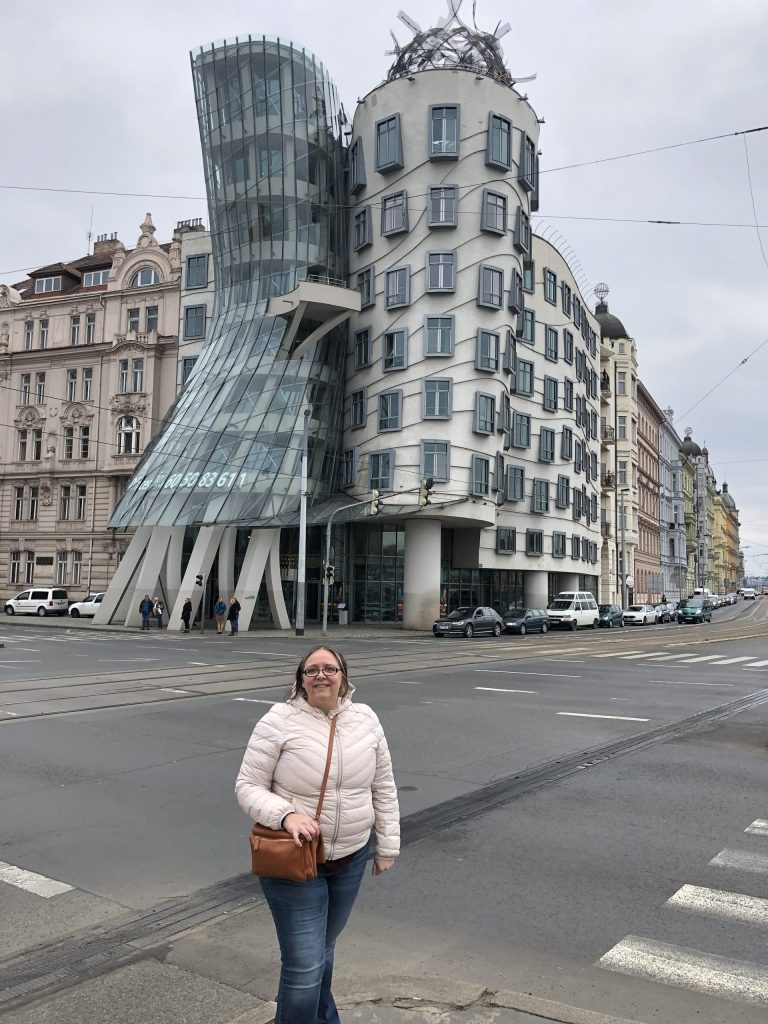 """Amy in a pink jacket in front of Frank Gehry's """"The Dancing House"""" building in Prague."""