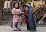 Two young girls play house, mimicking their mothers in burqas cut to their size, on the outskirts of Jalalabad, east of Kabul, on March 17, 2013. (AP Photo/Rahmat Gul)