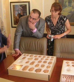 man and woman with camera looking at box of cuneiform artifacts on table