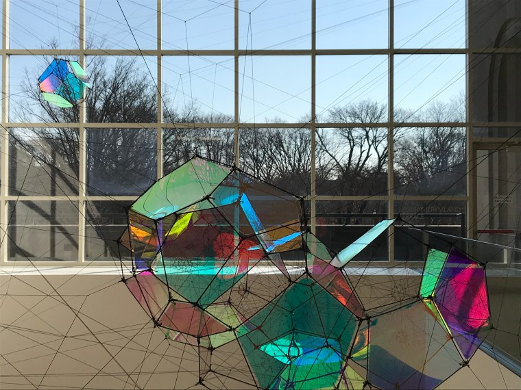 "modern stained glass sculpture in front of window - Tomás Saraceno ""Entangled Orbits"