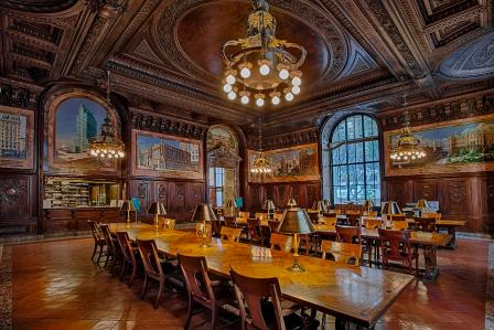 Room in library with large wooden tables and chairs, big windows, and a chandeleir