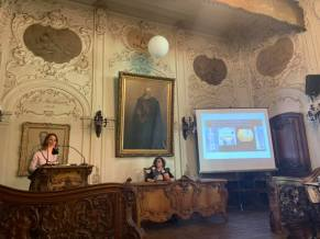 woman at microphone podium, woman at table, screen with projection on it