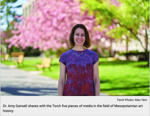 smiling woman in purple shirt standing in front of pink cherry blossom tree