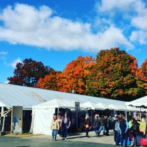 A busy fairground, with gorgeous fall foliage and blue skies in the background.