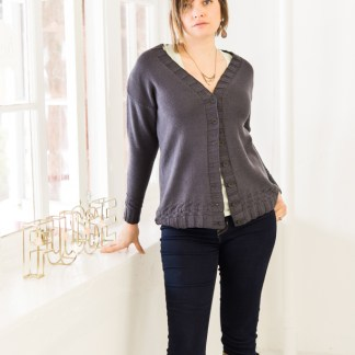 A woman in a straight-sided drop shoulder cardigan next to a window.