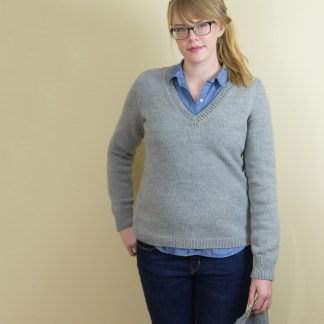 A woman in a tailored, well-fitting gray V neck pullover.
