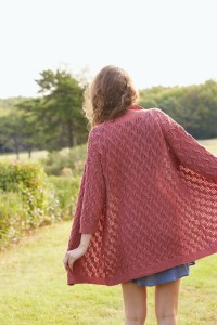 A woman in a swing-shape drop shoulder cardigan, viewed from the back