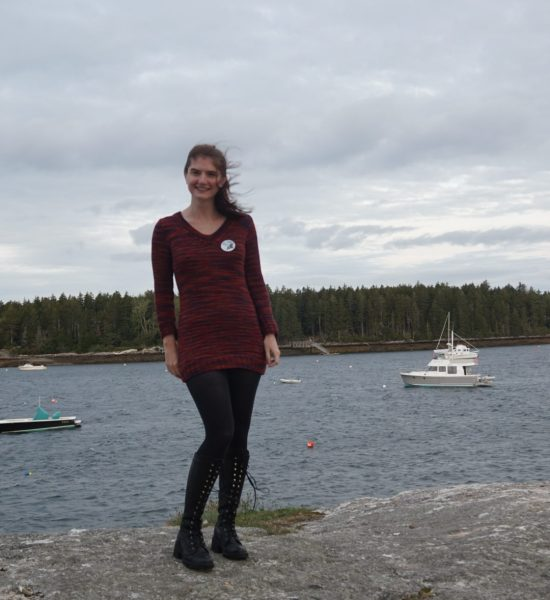 A petite white woman stands on rocks, with boats on the water behind her. She is wearing an orange and red long sweater, tights, and tall black boots.