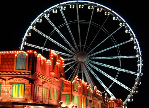 A ferris wheel illuminates the night sky above festive shopfronts at the Winter Wonderland Christmas market in London, England's Hyde Park.