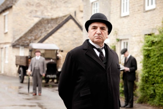 Jim Carter, better known as Mr. Carson the butler, casts a stern eye over the buildings of Downton village—actually the village of Bampton in Oxfordshire. Copyright Carnival Film & Television Limited 2012 for MASTERPIECE.
