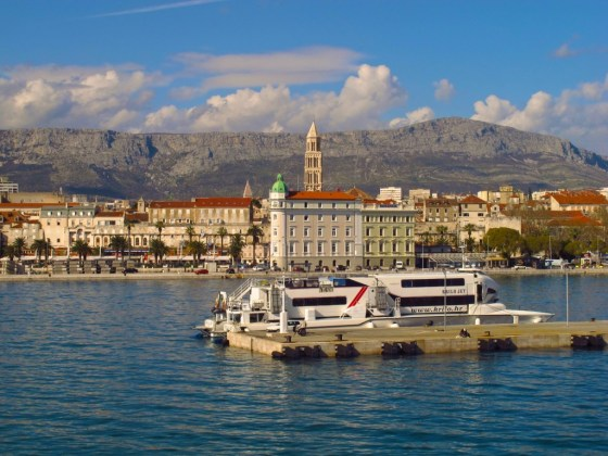A ferry awaits passengers in Split, Croatia. Beyond, the palm-fringed Riva promenade skirts the edge of the harbor and the Mosor Mountains rise up behind the city.