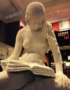 stone statue of a girl reading a book at Maison Assouline at 196A Piccadilly, London