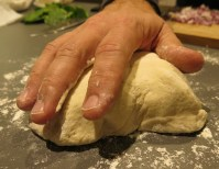 A big meaty handful of pizza dough should suffice for one pie.