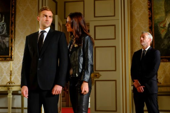 Tom Austen and Alexandra Parks, with Rocky Marshall as Agent James Hill on the set of The Royals. Courtesy E!