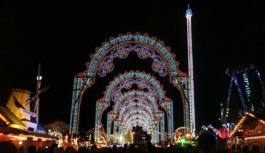 Crowds enter London's Hyde Park Winter Wonderland Christmas market beneath a lighted arcade.