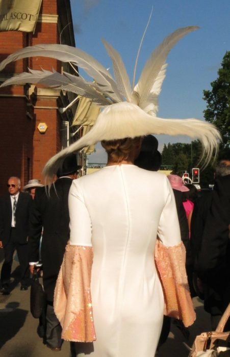 Rear view of a woman in a white feathered hat at Royal Ascot.