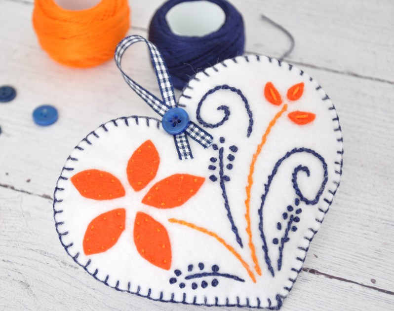 White felt heart charm with orange petals and navy blue embroidery