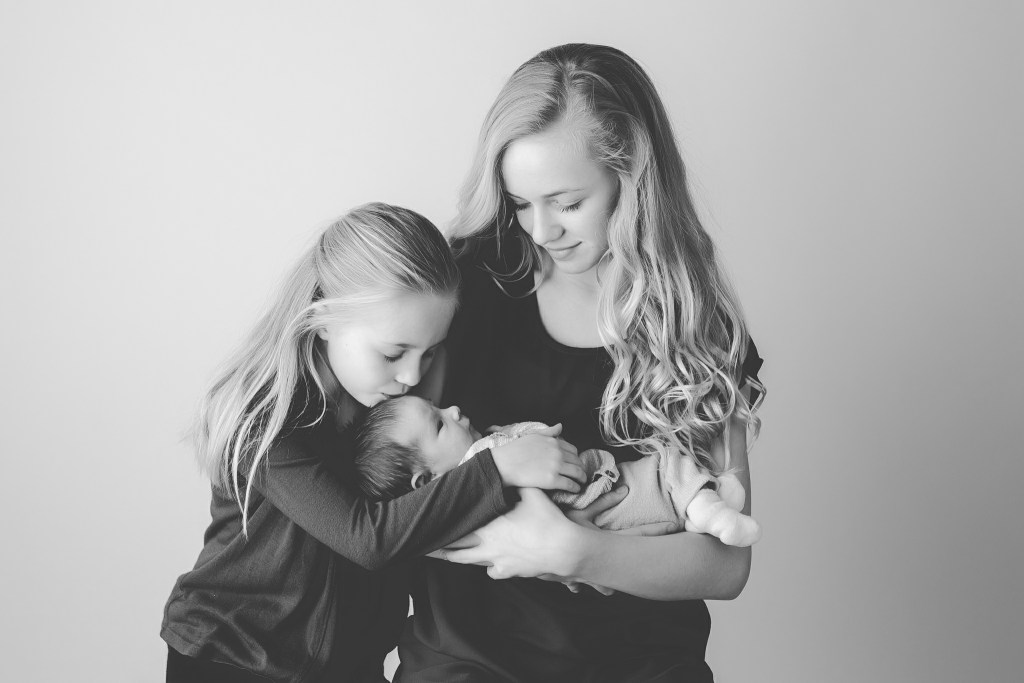 cousins holding newborn niece while kissing her