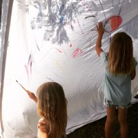 Use a plain white sheet for outdoor painting for kids! We used watercolors and created a beautiful tent. This is a great project for a lazy Summer day.