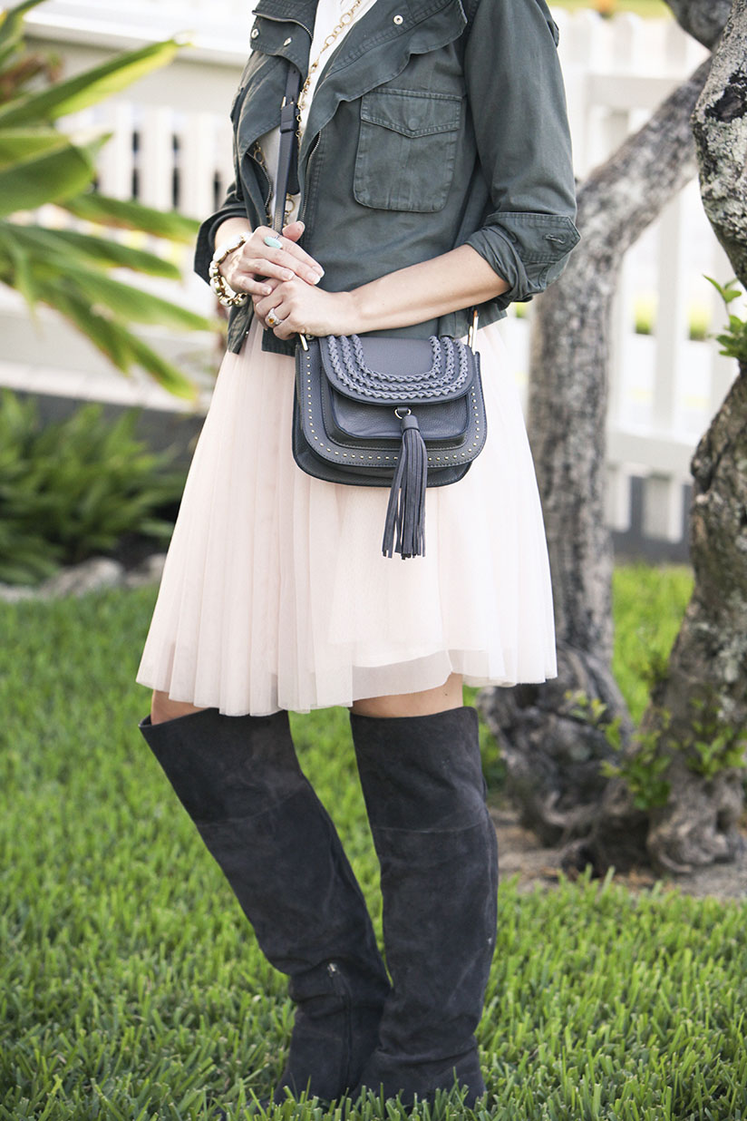 Amy West wearing military jacket, and western cross body bag