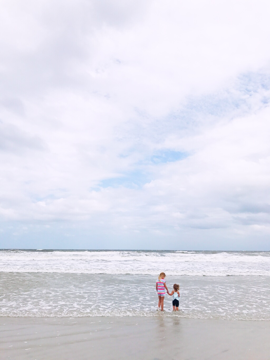 Two sisters observe the surf before a hurricane