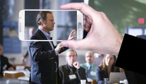 Man speaking in public and person taking a photo of them to illustrate thought leadership.
