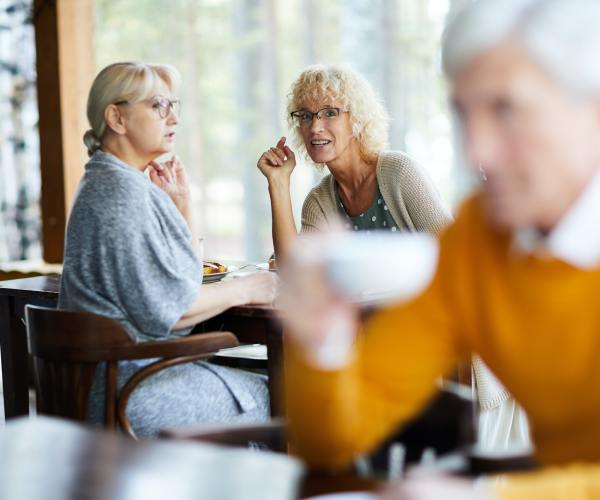 Mature ladies gossiping about handsome man in cafe
