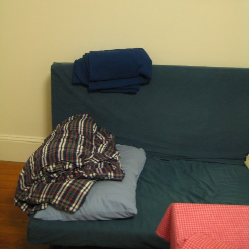 Photograph of futon in dark teal slipcover with blankets and pillow