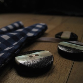 Detail photograph of mother of pearl and wood buttons, blue gingham bag, and white ribbon