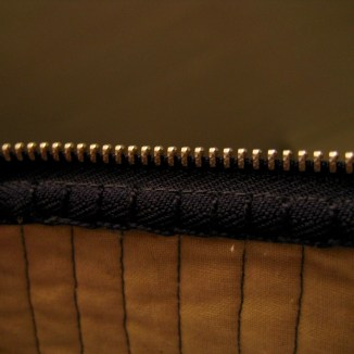 Detail photograph of interior top edge of open zipper pouch, showing metal zipper teeth, quilted muslin, and blanket stitching to secure edge of zipper