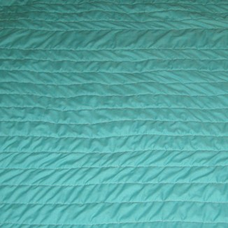 Detail of aqua baby quilt showing solid aqua section with lines of quilting